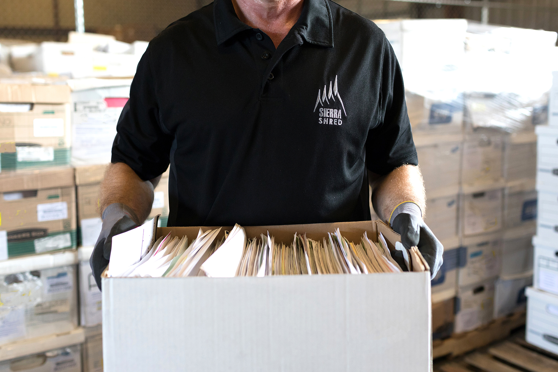man with boxes of paper that need to be shred.